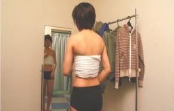 胸にサラシをまいて鏡の前に立つ純