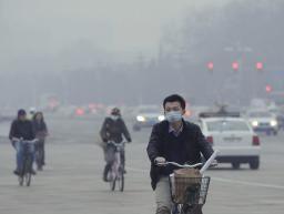大気汚染が深刻化し、マスクを着けて自転車に乗る男性=3月、北京(共同)