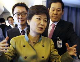 5日、米国に向かう機内で記者団にあいさつする韓国の朴槿恵大統領と、同行した尹昶重元報道官(左後ろ)(聯合=共同)
