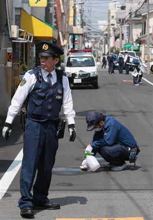 路上で刃物で男女2人が刺された現場付近を調べる捜査員ら=22日午前9時50分、大阪市生野区(山田哲撮影)