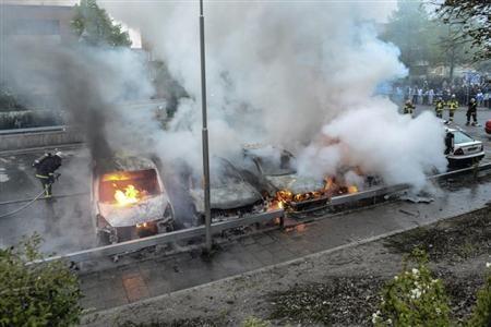 5月23日、スウェーデンの首都ストックホルム郊外で起きた暴動は、同国の「移民寛容政策」の負の一面を浮き彫りにした。写真は消火に当たる消防隊員ら