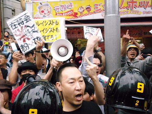 5月19日【通名制度の悪用をなくせ!デモin新大久保】で、デモ隊に「ぶっ殺す!」と中指を立てたり、「くたばれ!」「死ね!」などとヘイトスピーチを浴びせるレイシストしばき隊(在日韓国人、在日朝鮮人、反日極左