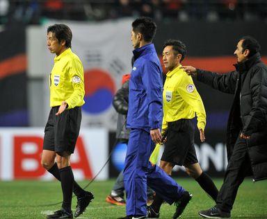 カタールの首脳陣から試合後に抗議を受ける西村雄一(Yuichi Nishimura)主審(左、2013年3月26日撮影)