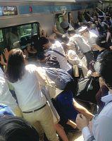 電車とホームの間に挟まれた女性を救出するため、車両を押して傾ける乗客や駅員ら(22日午前9時19分、JR南浦和駅で)=繁田統央撮影