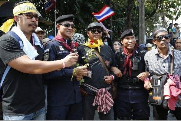 2014-1-11タイの反政府デモで小競り合いを止め記念撮影する警察隊長とデモ参加者12月3日