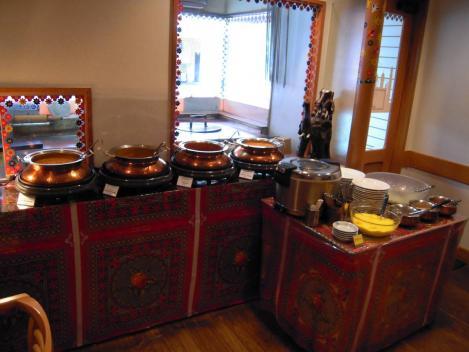 インドカレー店のカレーソース各種が並べられ裏にはナンを作る工房がある