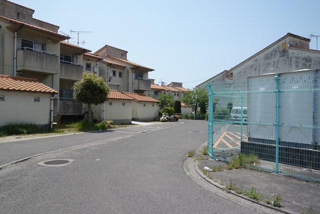 カーブした道と松前町営江川団地の住棟