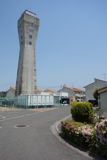 カーブした道と松前町営江川団地給水塔